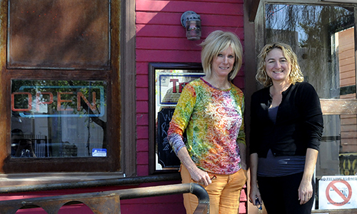 The Groove on Grand property owner Laurie Carmody (left) and Red House Pub owner Tanya Craven (right) stand in front of Red House Pub, one of the Groove businesses housed inside former WWII prisoner of war cottages. (Danika Worthington/DD)