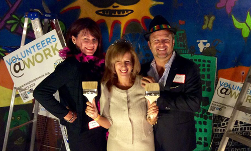 "(left to right) - Melissa Lewis, owner of Table Tops, Etc. and one of HandsOn's founding board members, (middle) Alison Rapping, former HandsOn CEO and Albin Halquist, President of Halquist Construction and one of HandsOn's founding board members. They are taking a picture in our 21st birthday ""photo booth"" which utilized some of the great murals that are a part of the lot/pop up park. (Photo Courtesy of Chris Helmuth)"