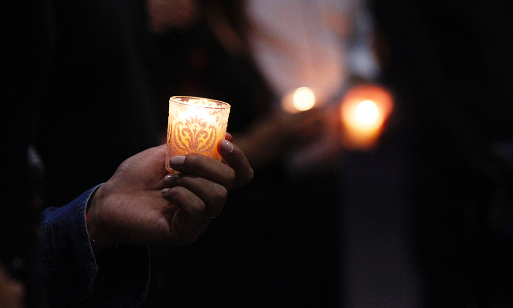 """Attendees held candles while singing """"Lean on Me"""" together. (Nicole Neri/DD)"""
